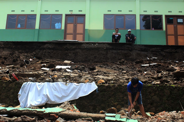 Sejumlah warga sekitar membersihkan puing-puing bangunan rubuh di MI Fathul Khaer, Kampung Pasir Angin, Desa Cilengkrang, Kecamatan Cilengkrang, Kabupaten Bandung, Minggu (13/11). Ambruknya bangunan diakibatkan curah hujan yang tinggi sehingga debit air naik serta diperparah oleh retakan pada beberapa bagian banguna. Tidak ada korban jiwa tetapi kerugian ditaksir mencapai 30 juta. (Jurnalpos/Ridha Achmad).